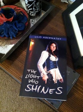 Picture of The Light Who Shines book on Michelle's table, featuring the first version of the cover.